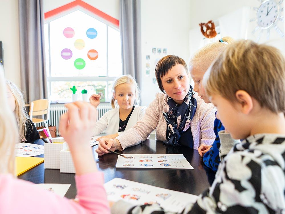 En lärare på Thoren Framtid som sitter ned vid ett bord tillsammans med tre elever