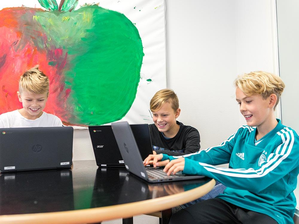 Tre elever som jobbar vid sina bärbara datorer