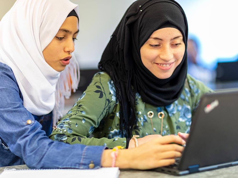 Två elever med Hijab som sitter vid en bärbar dator