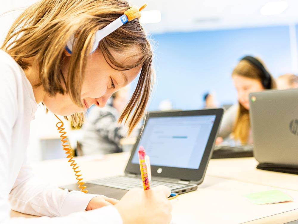 En flicka på Thoren Framtid Grundskola sitter med hörlurar och en bärbar dator och skriver med penna