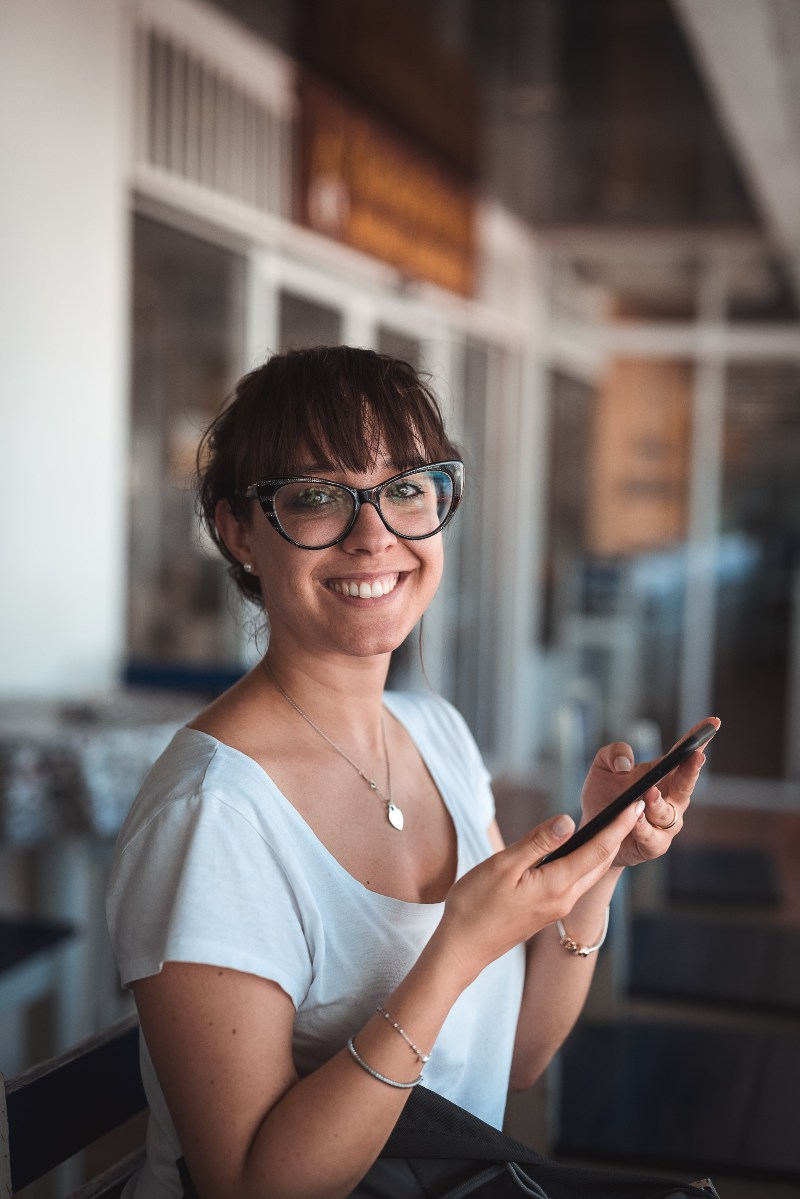 woman in glasses smiling holding smartphone