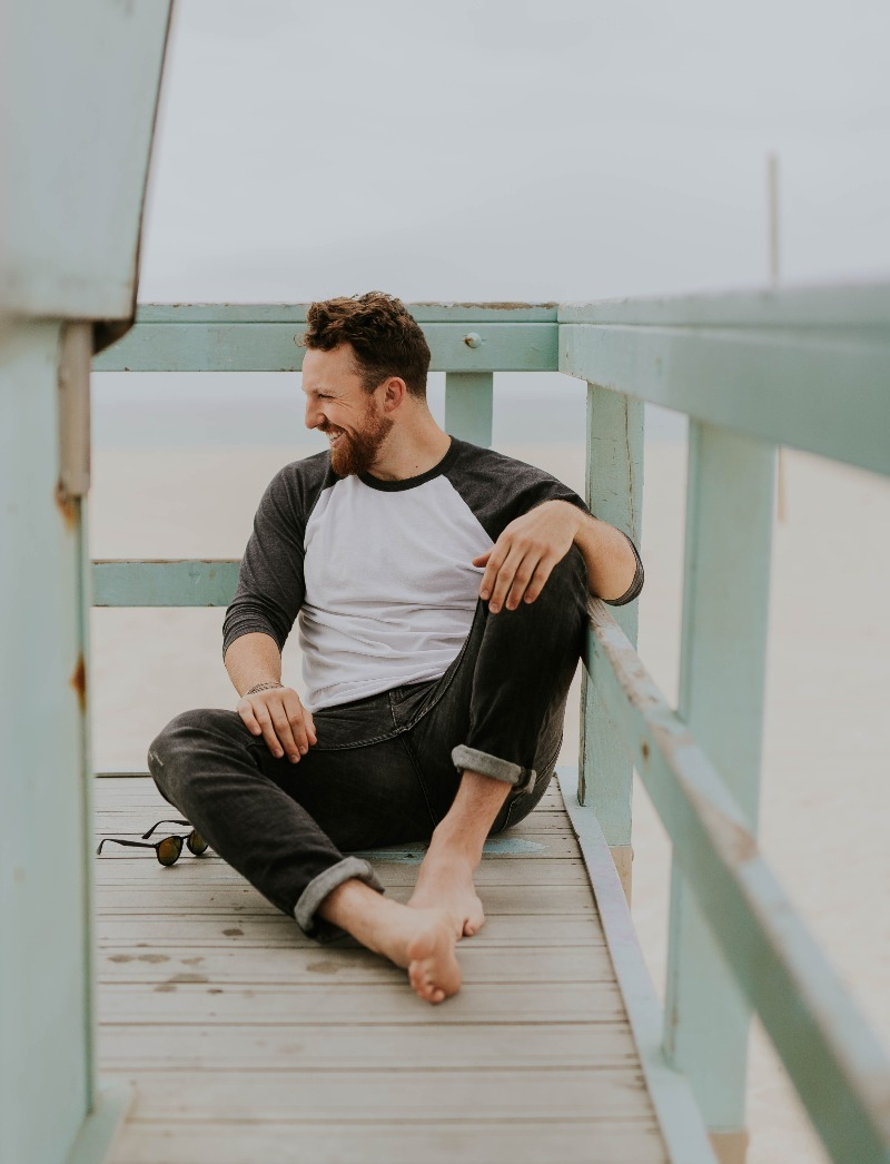man smiling on dock with no shoes
