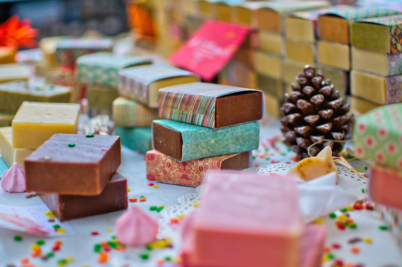 Photo of a table with piles of handmade soaps, confetti, and a pinecone.