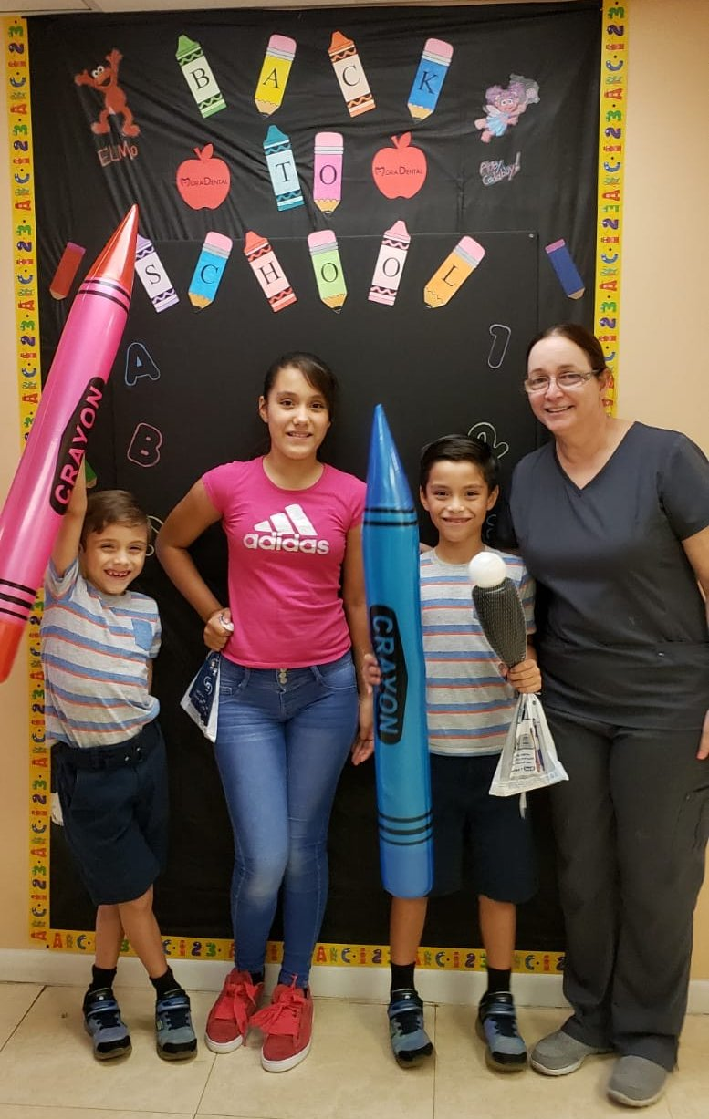 dental hygienist with 3 patients smiling in front of back to school sign