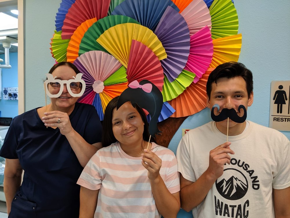 a dental hygienist and 2 patients using fun props to take a picture
