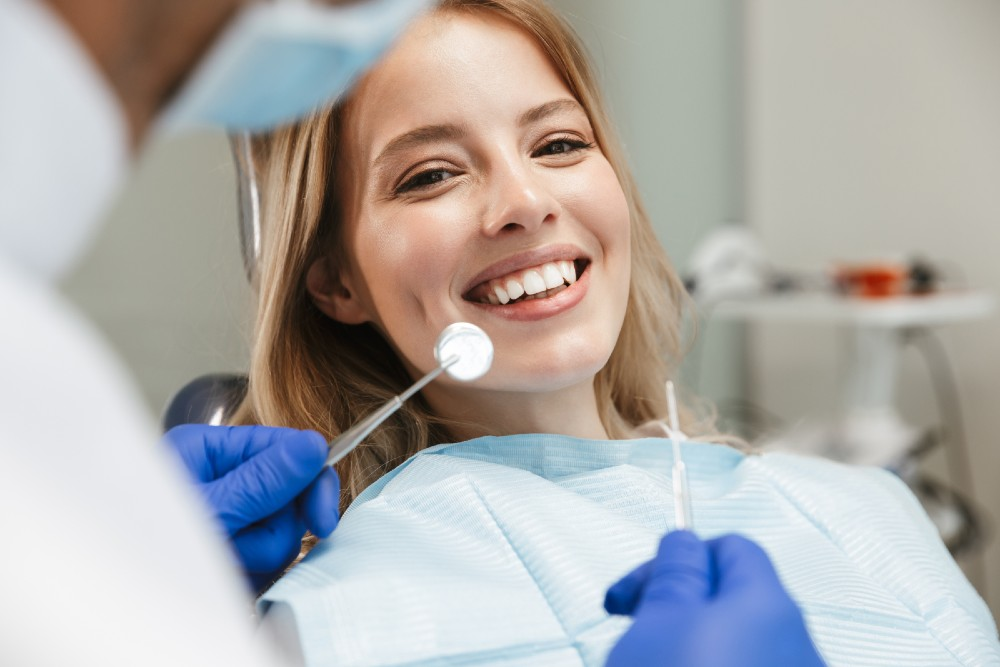 woman smiling at doctor as he is getting ready to check her teeth