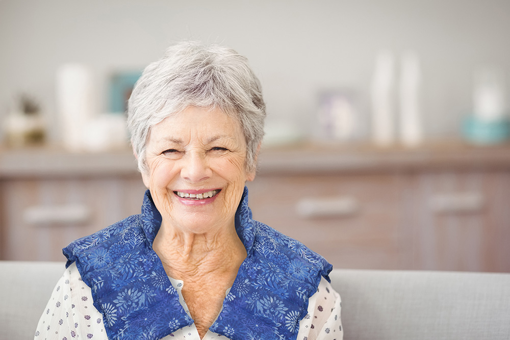 Senior woman wearing a heating neck pad