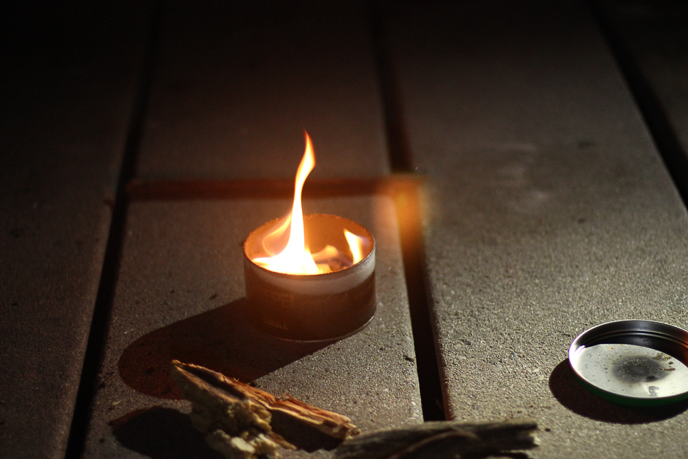 Small fire inside tin can on picnic bench