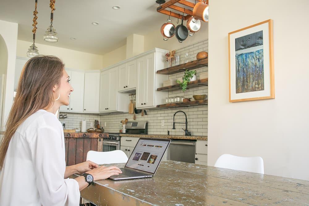 Woman controlling her Canvia digital art smart frame