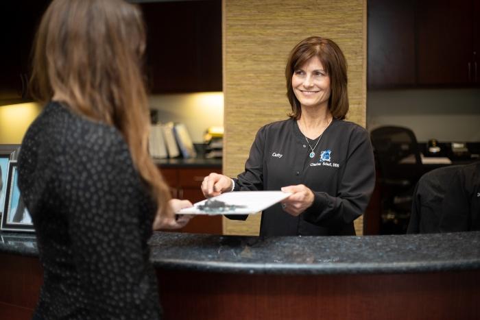 Receptionist handing patient new patient forms