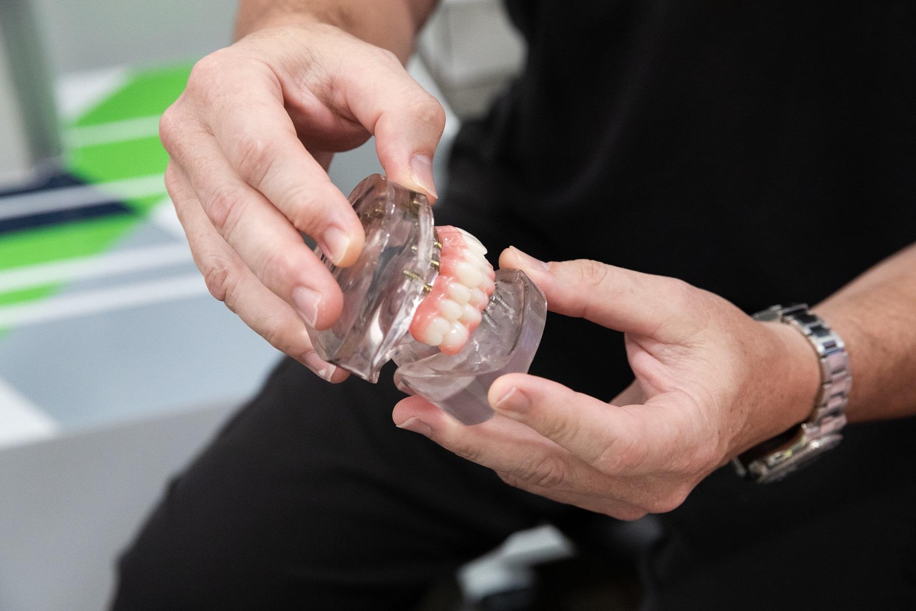 Dr. Schof showing a patient a dental implant