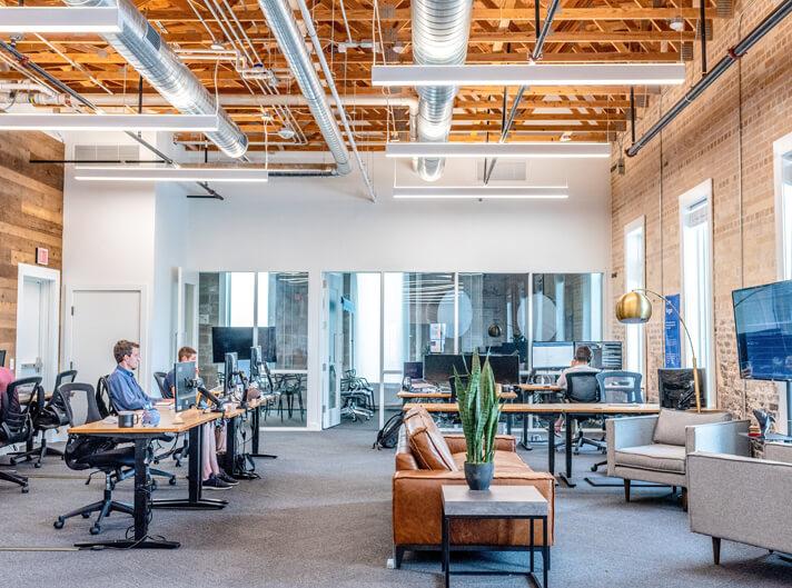 Bilde med mange som sitter i ett kontor.