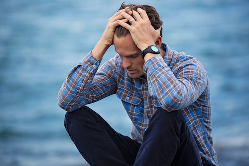 man with anxiety with hands in hair sitting in front of ocean