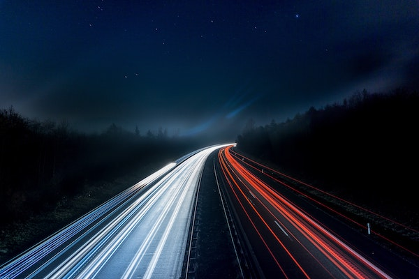 Red and white light trails from cars travelling along a highway at night through a forest under the stars