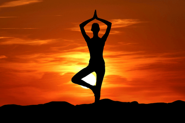 a silhouette of a women doing a yoga stand in front of a bright orange and red sunset