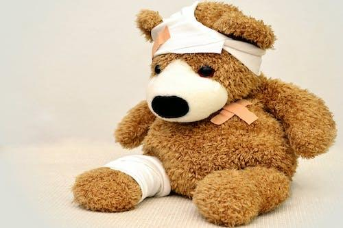 teddy bear bandaged with bandaids after a painful incident