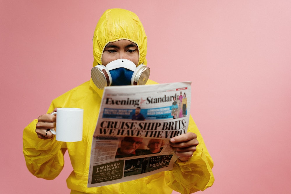 man holding a mug in a hazmat suit reading the newspaper
