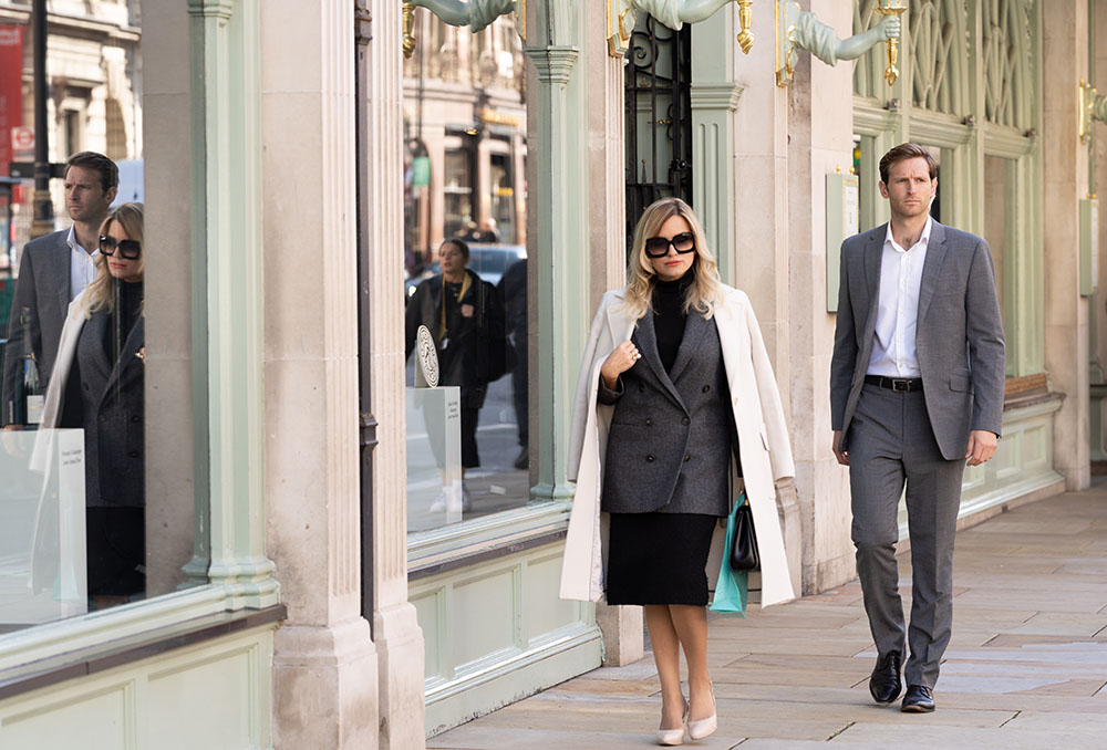 Bodyguard walking behind high-profile client in street.