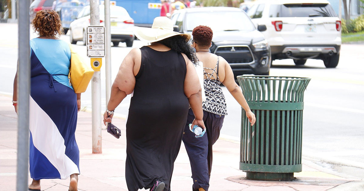 photo of obese people walking in the street