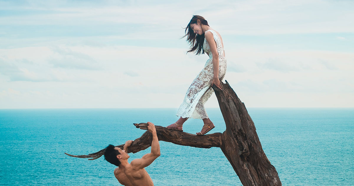 Man using his muscles to climb tree with woman standing above him