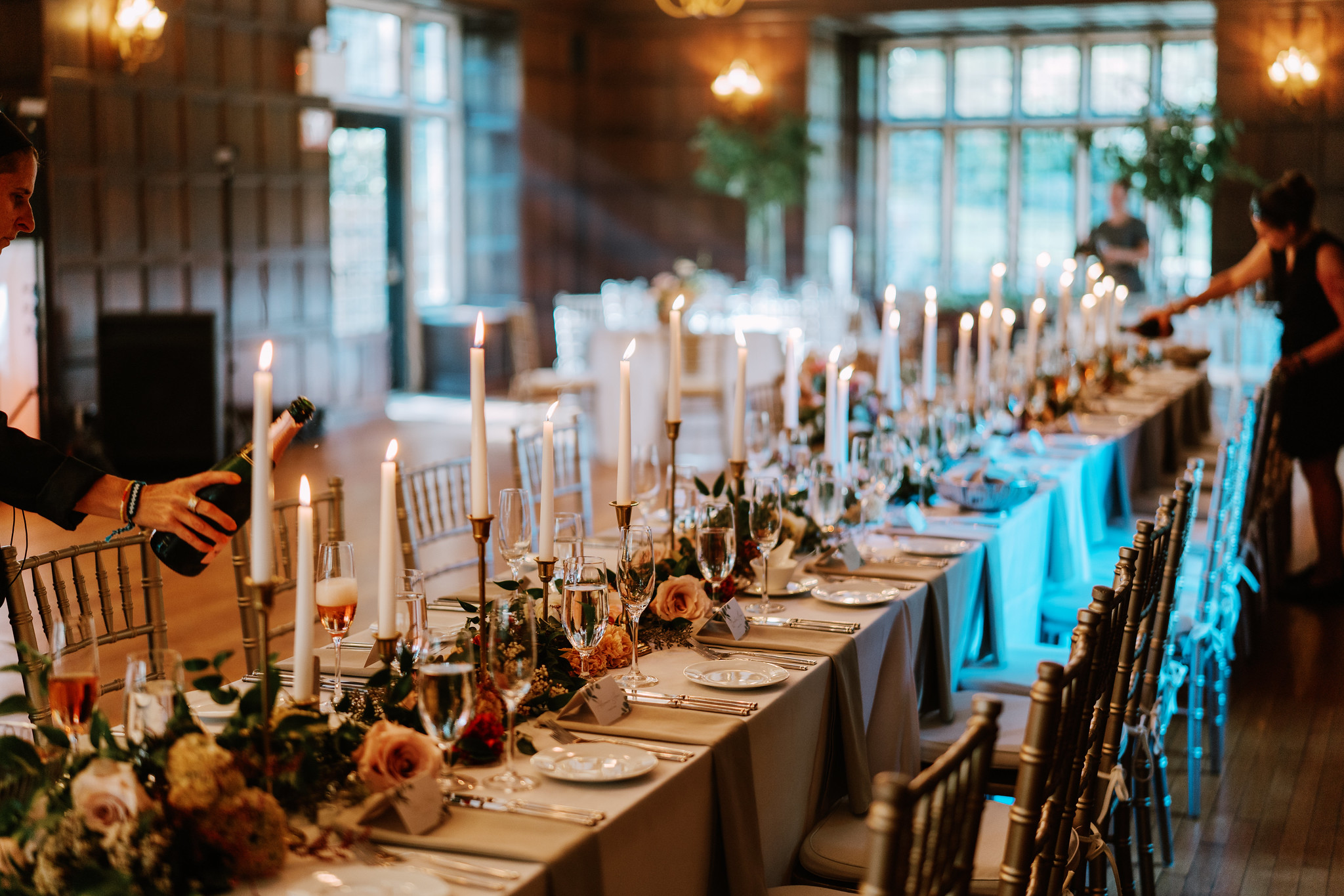 Long, elegant communal table with candle sticks, wild flowers, and wine glasses.