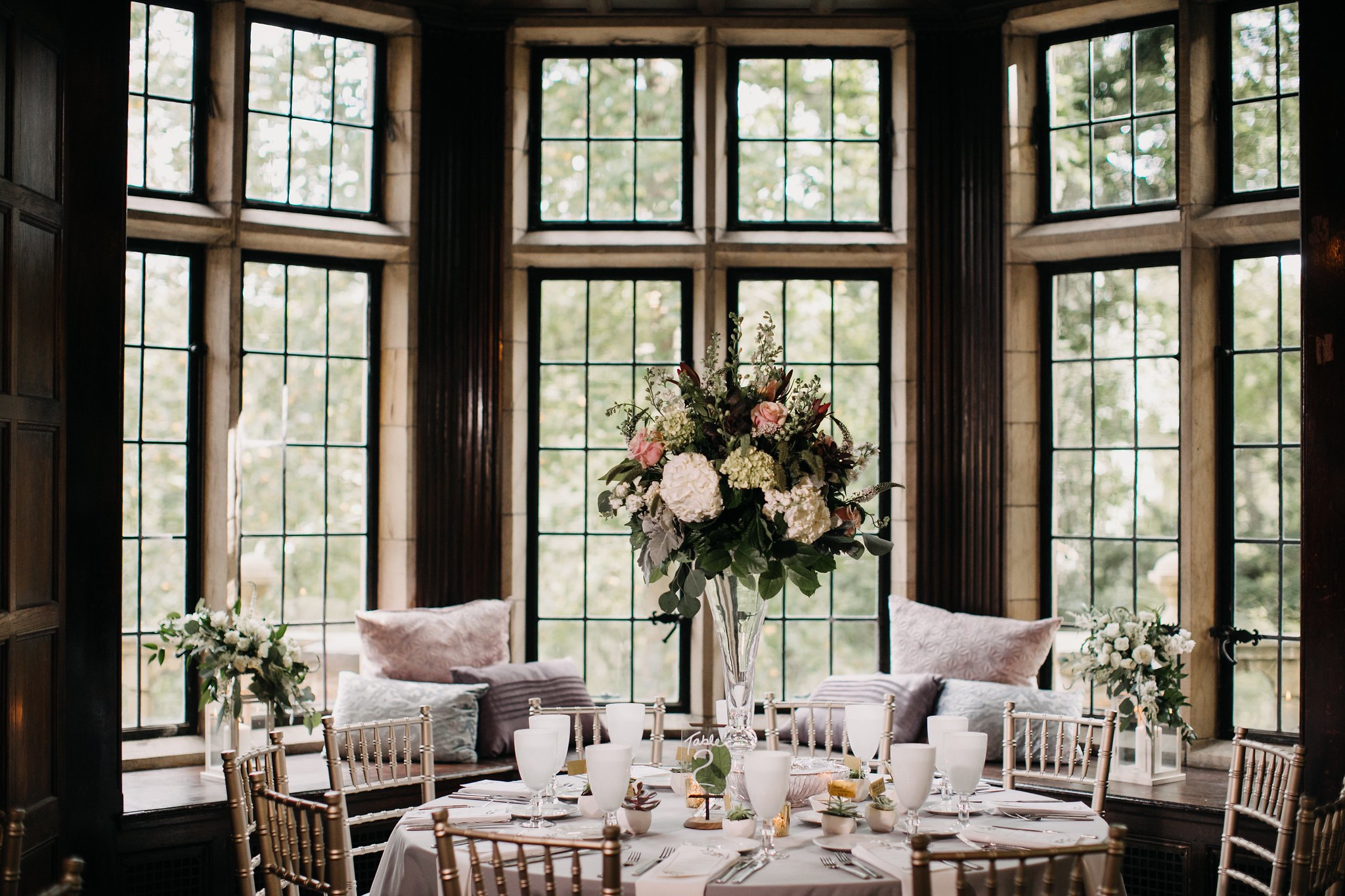 Flowers with greenery in a vase on a round table by large windows.