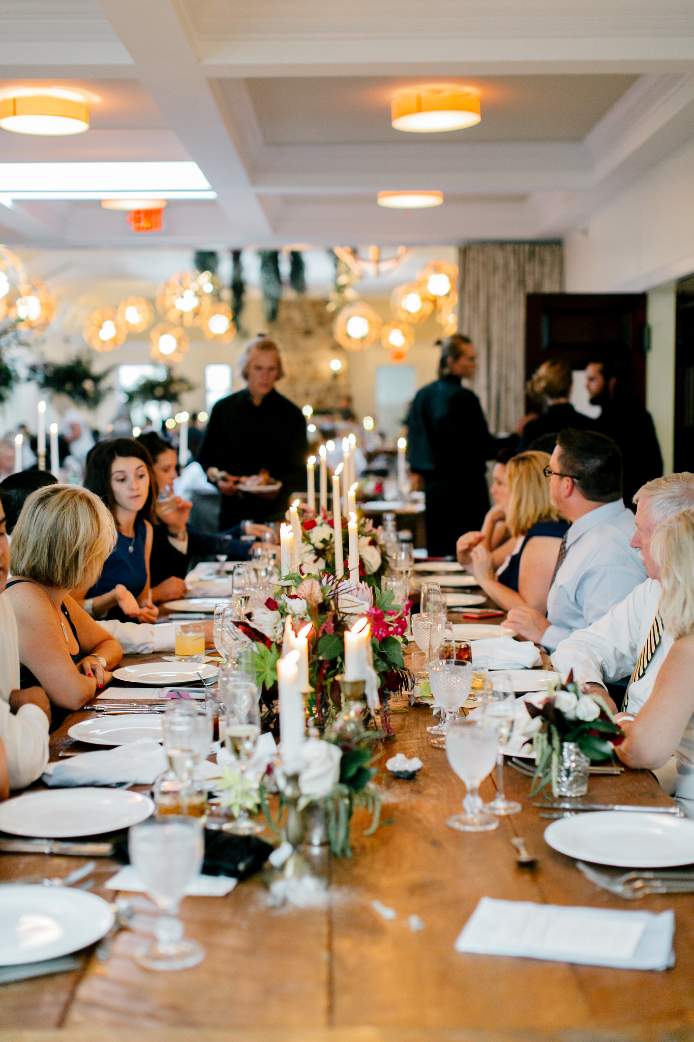 Corporate gathering at a long communal table with fresh wild flowers and candle sticks.