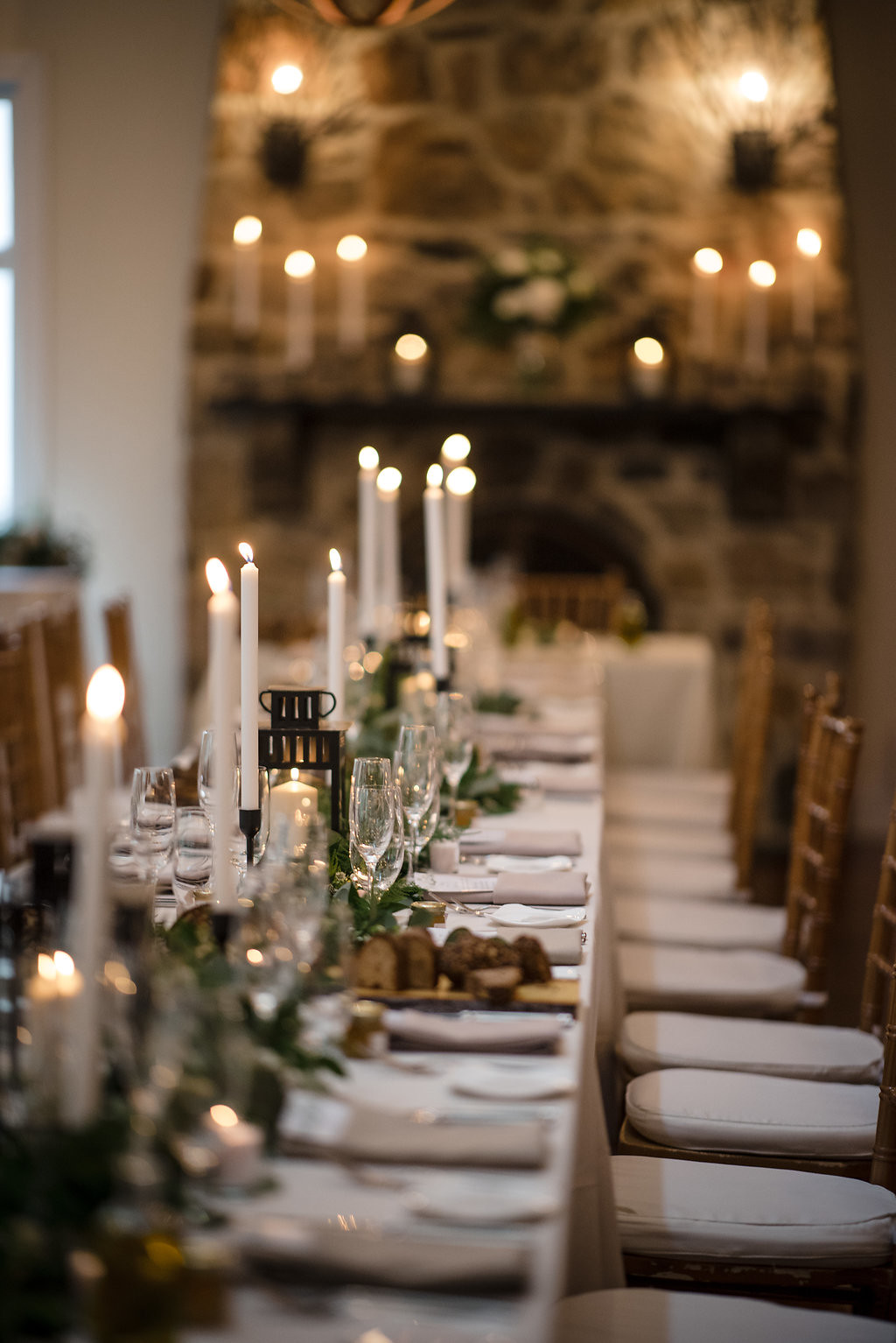 Long communal table with greenery and candle sticks.