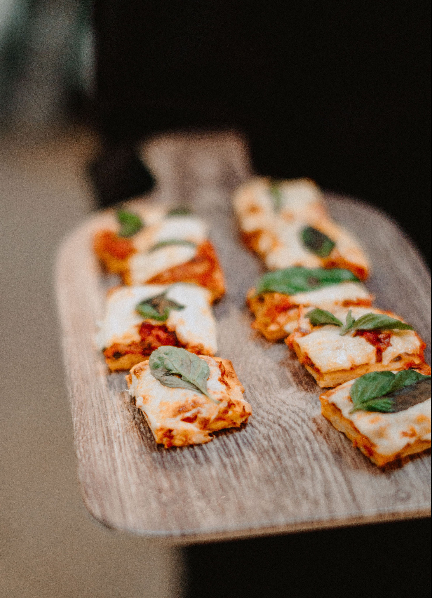 Lasagna being served as hors d'oeuvres on a rustic wooden board.
