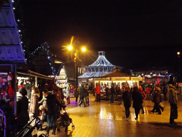 Evening photo of the Bournemouth Christmas Market held in the Square. Groups of people stood in shop doors looking at their wears.