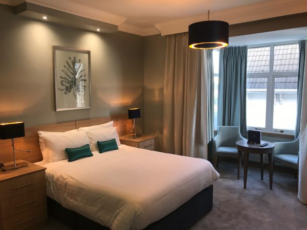 Hotel Collingwood Double bed room fitted with 2 bedside tables, lamps and a room phone. Over bed lighting and modern lamp brigten the room with the bay windows open. 2 armchairs and a table sit in the bay window area.