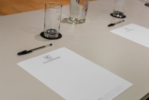 close up of the provided paper and pens with the Hotel Collingwood branding. Glasses rest in front of each piece of paper with jug of water in the background