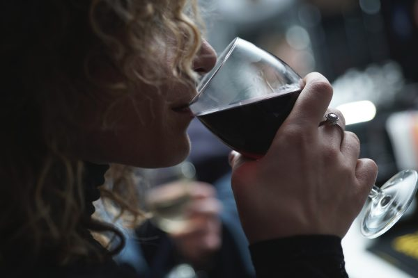 woman taking a sip of red wine