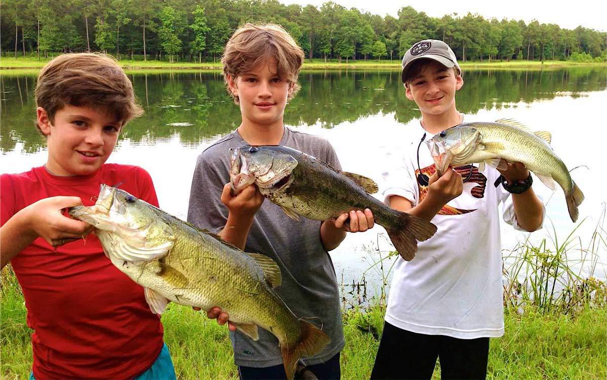 three boys with fish in front of a pond
