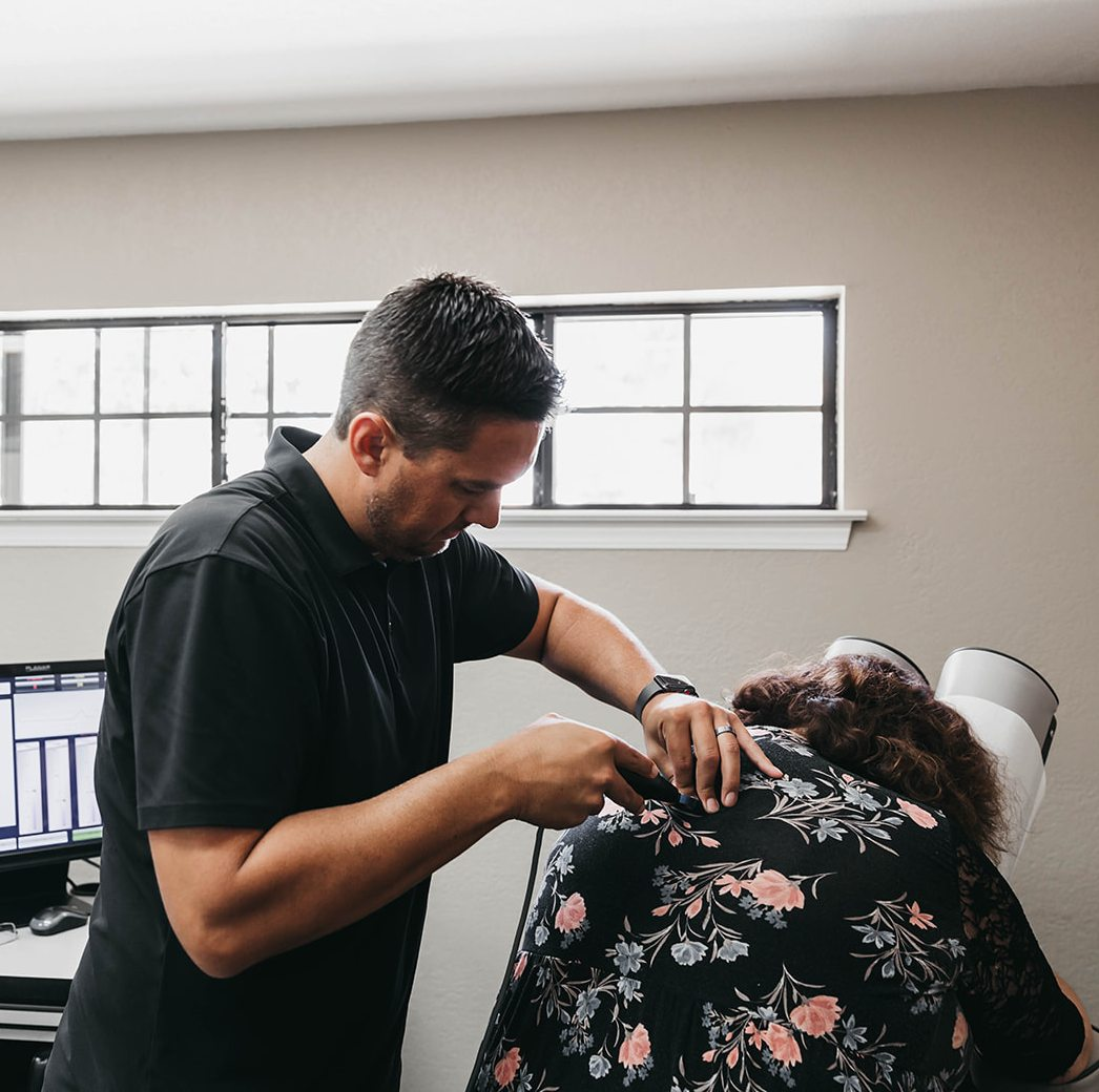 Dr. Beau helping a woman with her back