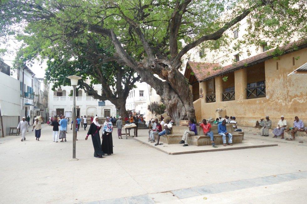 Skyggen under trærne på bytorget er en natrulig møteplass