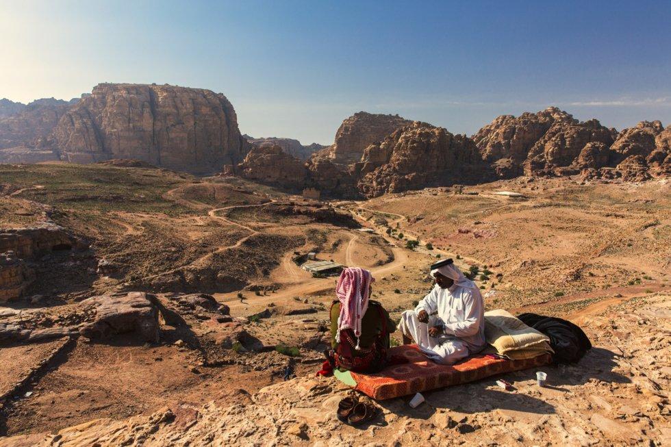 Beduiner slapper av i det sandblåste landskapet.