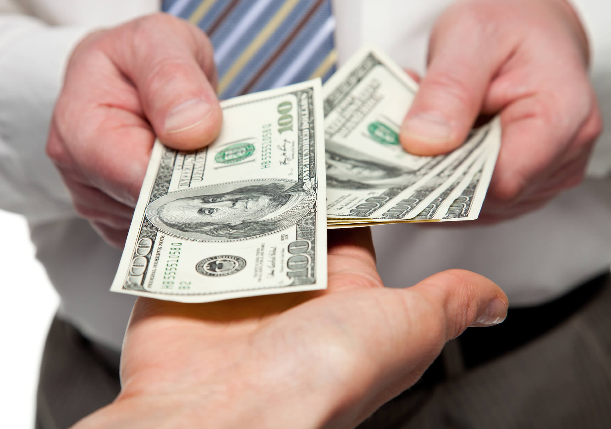 man-handing-dollar-notes-to-another-person