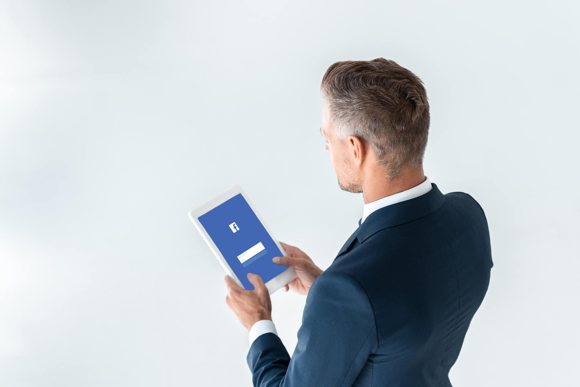 businessman-holding-tablet-with-facebook-login