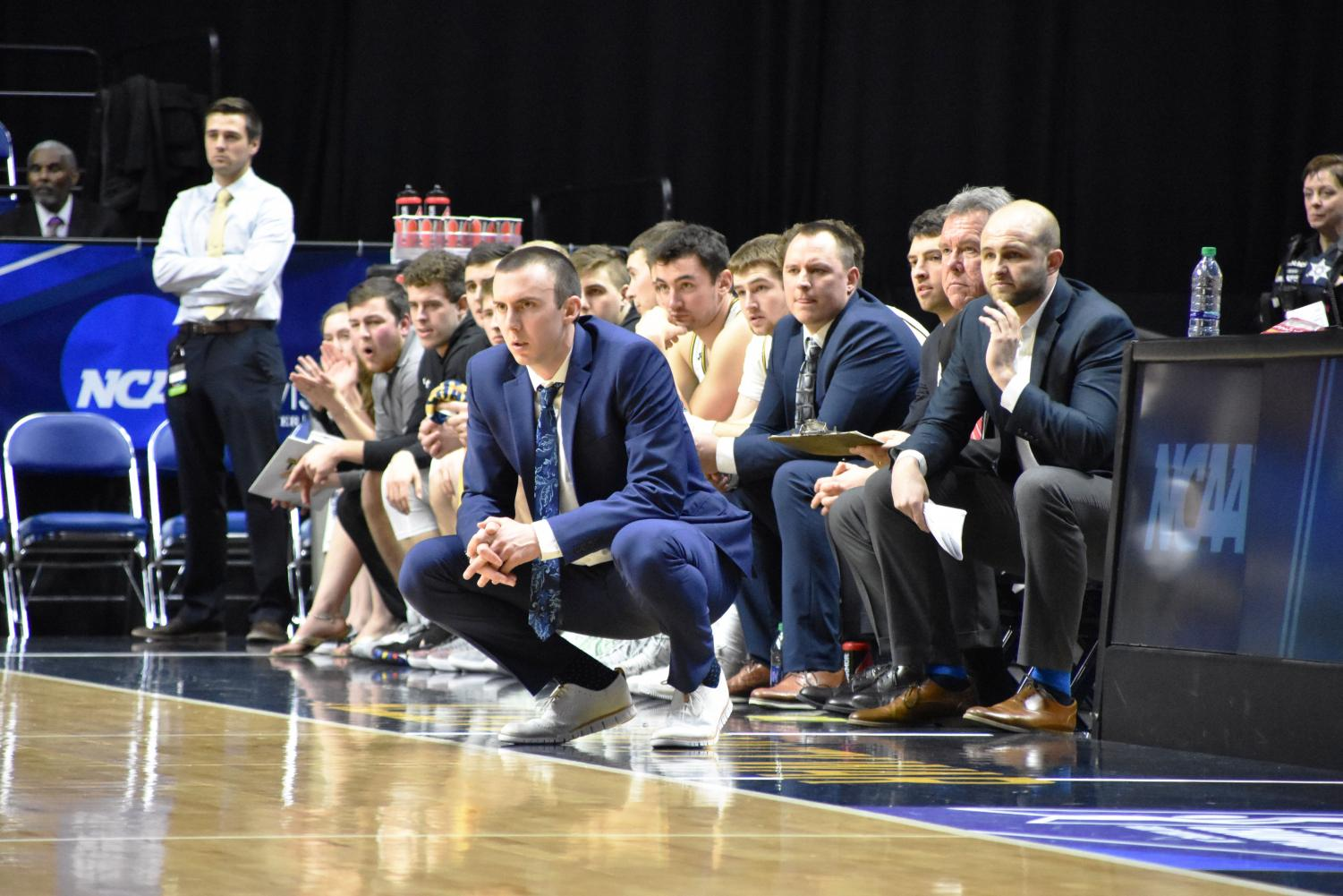 UW Oshkosh Head Coach Matt Lewis crouches during a game in 2019.  Credit: Lydia Sanchez, The Advance Titan