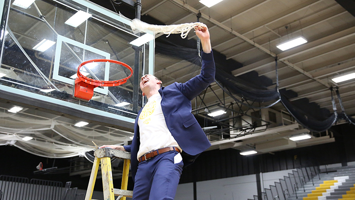 Matt Lewis cuts down the net after winning the NCAA D3 National Championship in 2019.  Credit: Liz Smith, UW Oshkosh Today.