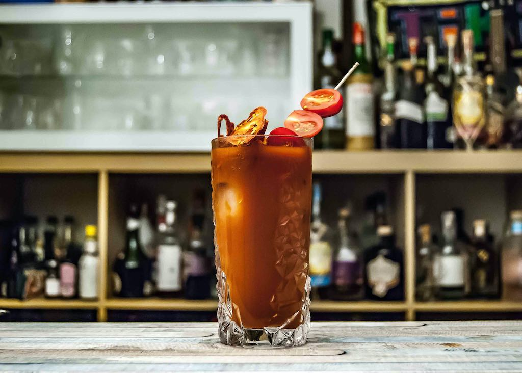 a bloody mary with a tomato skewer garnish