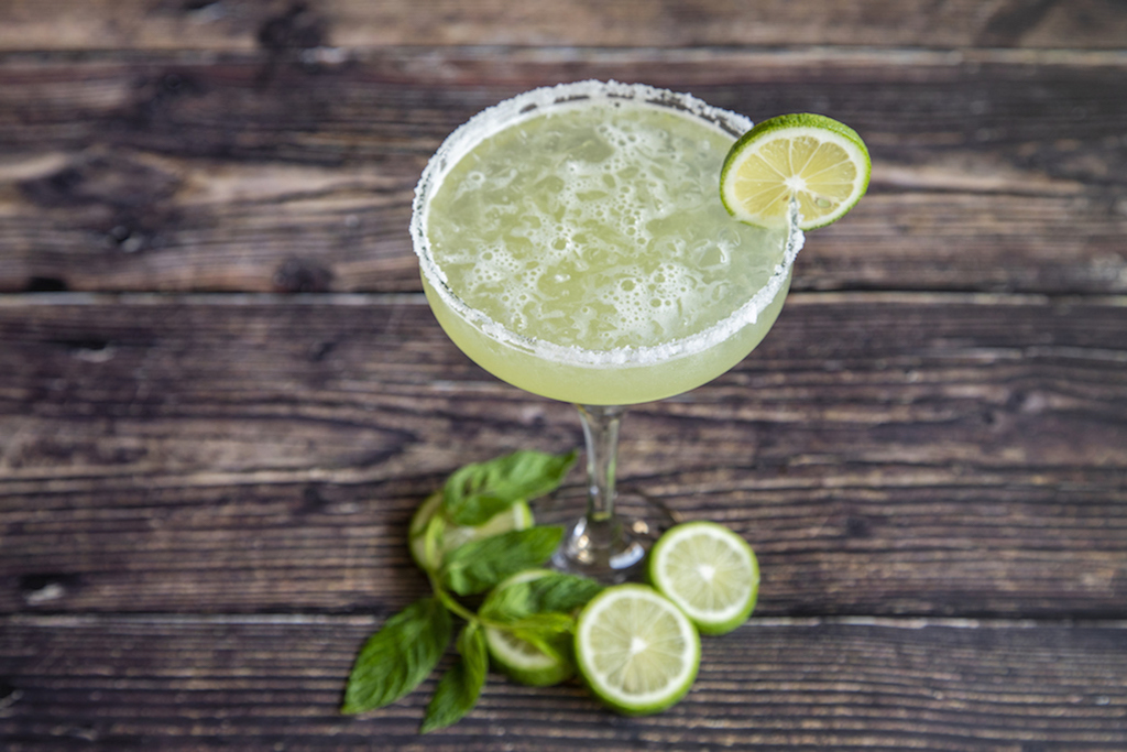 A margarita with a salted rim and lime wheel garnish