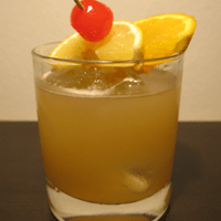 whiskey sour with orange slices and a cherry