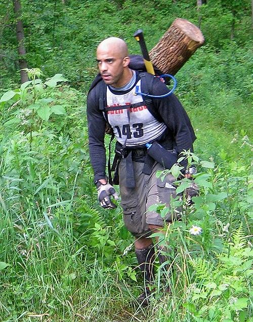 Josh Zitomer walking with log on back doing Spartan Death Race