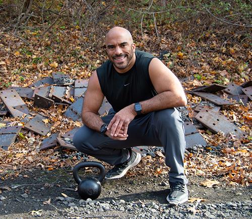 Josh Zitomer crouching next to kettlebell by train tracks