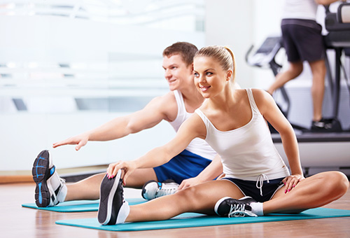 Four people in workout clothing smiling