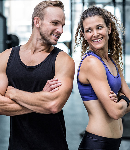 Two women in workout clothing smiling