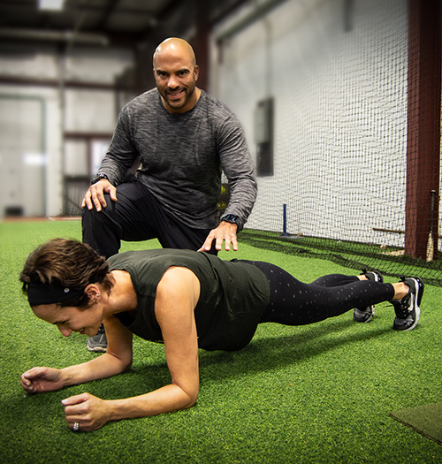 Man and woman in workout clothing doing forward lunges