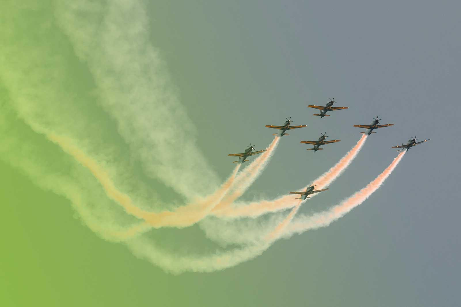 Fotografia de um esquadrão de aviões em vôo fazendo manobras